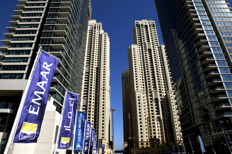 Flags of Emaar Properties PJSC, builder of the world's tallest skyscraper, fly near high-rise properties in the Marina district of Dubai, United Arab Emirates, on Saturday, Dec. 10, 2011. Dubai and its state-owned non-financial companies have $101.5 billion of outstanding debt and may need further financial support to meet those obligations, Moody's said. Photographer: Gabriela Maj/Bloomberg